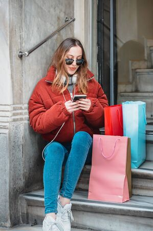 Beautiful young girl in fashionable clothes rests and uses smartphone on stairs after shopping.Modern young girl lifestyle or travel tourist concept