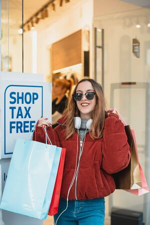 Beautiful attractive young girl in jumper and jeans with sunglasses and bags exits from shopping store