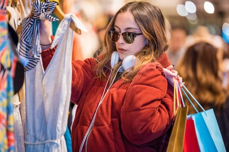 Beautiful attractive young girl in jumper with headphone and sunglasses chooses clothes, thinking looking at clothes while shopping in store