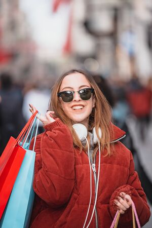 Beautiful attractive young girl in jumper and jeans with sunglasses and bags walks at a crowded street after shopping