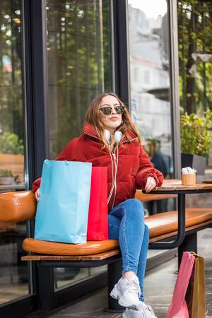 Beautiful young girl in fashionable modern clothes sits in a cafe after shopping.Modern young woman lifestyle or travel tourist concept