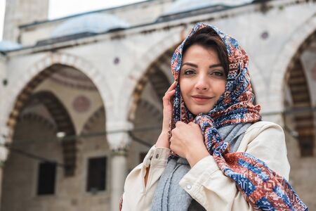 Beautiful Muslim woman in head scarf and fashionable modern trendy clothes poses at courtyard of  Blue Mosque,a popular destination in Istanbul,Turkey Stock Photo