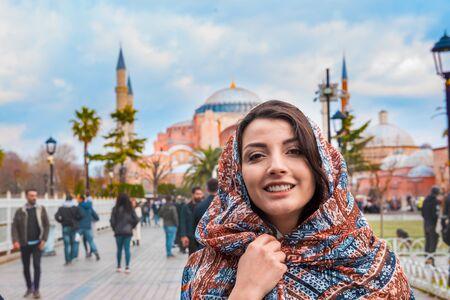 Beautiful Muslim woman in head scarf poses at Sultanahmet Park, a popular destination in Istanbul,Turkey Фото со стока