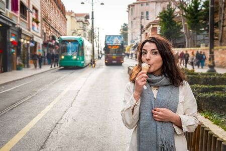 Beautiful young girl in fashionable clothes walks while eating ice cream in Istanbul,Turkey.Traveler woman  lifestyle Concept.