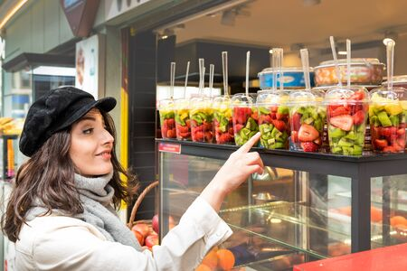Beautiful young girl shows different sliced fruits in plastic cups sold a store stall vehicle in Istanbul,Turkey.Traveler woman  lifestyle Concept. Imagens