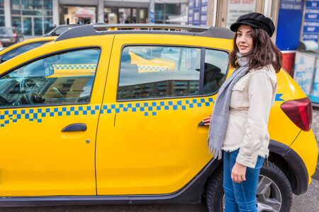 Beautiful young girl opens or closes door of a yellow taxi with her hand.Traveler woman lifestyle Concept.