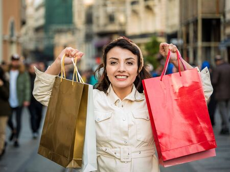 Beautiful attractive young girl in fashionable clothes holds shopping bags after shopping while walking at street. Happy woman with shopping bags.Shopping, lifestyle concept 版權商用圖片