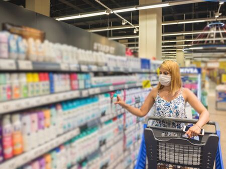 Young beautiful woman with shopping cart wears medical mask against coronavirus while shopping deodorant and stockpiling in supermarket. Shopping concept during pandemic corona,covid19.