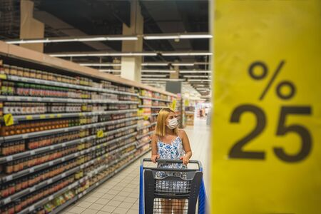 Young beautiful woman with shopping cart wears medical mask against coronavirus while grocery shopping and stockpiling in supermarket. Shopping concept during pandemic corona,covid19. Stok Fotoğraf