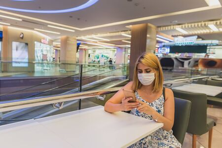Young beautiful woman wearing face mask and keep social distance by sitting alone on each table in the restaurant during covid-19 or coronavirus outbreak .