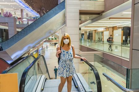Young beautiful woman wearing face mask and keep social distance while using escalator in a big shopping center during coid19 outbreak