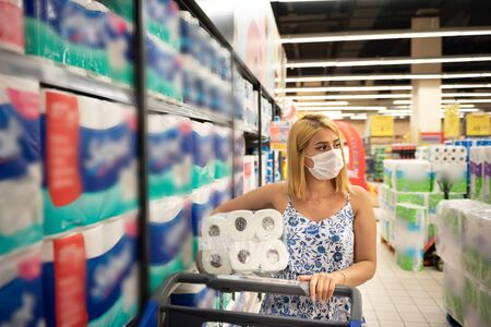 Young beautiful woman with shopping cart wears medical mask against coronavirus while shopping and stockpiling toilet papers and tissue in supermarket during pandemic corona,covid19.