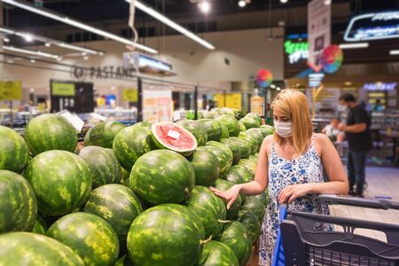 Young woman with shopping cart wears medical mask and  buys watermelon fruits. Shopping during the Coronavirus Covid-19 epidemic 2020
