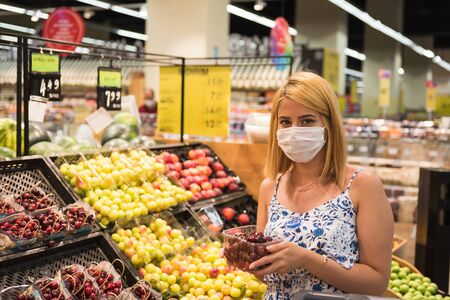 Young woman with shopping cart wears medical mask and  buys cherries fruits. Shopping during the Coronavirus Covid-19 epidemic 2020
