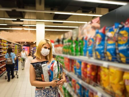 Young beautiful woman with medical mask holds potato chips packs while shopping and stockpiling in supermarket. Shopping concept during pandemic corona,covid19.