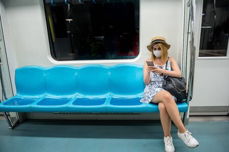 Young beautiful woman wears face mask and keeps social distance by sitting alone while transporting at train during covid-19 or coronavirus outbreak .