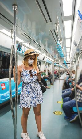 Young beautiful woman wears face mask and keeps social distance by standing and using smart phone while transporting at train during covid-19 or coronavirus outbreak Stok Fotoğraf
