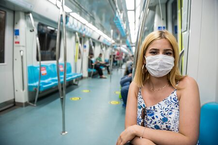 Portrait of happy beautiful woman wearing protective face mask and keeps social distance by sitting alone with smile during covid-19 or coronavirus outbreak . Stok Fotoğraf