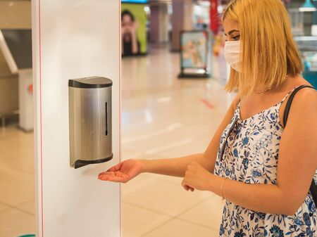 Portrait of beautiful woman wearing protective face mask uses automatic hand sanitizer dispenser at the entrance of shopping center during covid-19 outbreak . Stok Fotoğraf