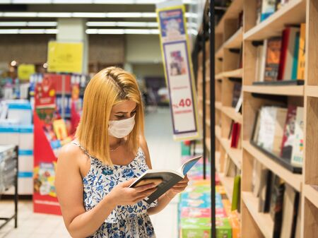 Portrait of beautiful woman wearing protective face mask  checks book in book store during covid-19 outbreak.The new normal life social distancing for protect coronavirus or covid-19.
