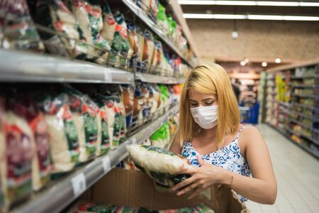 Young woman with medical mask picks up rice pack at Supermarket and stockpiling during pandemic corona,covid19. Stok Fotoğraf