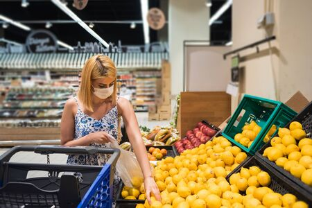 Young woman with shopping cart wears medical mask and buys lemons and fruits. Shopping during the Coronavirus Covid-19 epidemic 2020