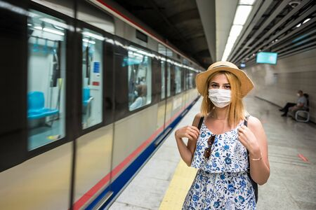 Portrait of young beautiful girl in disposable face mask waits for train on subway platform. Concept of prevention and social distancing in coronavirus,covid19 pandemic