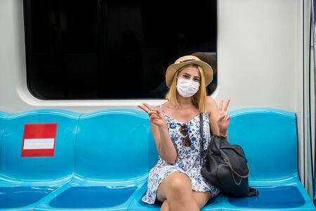 Portrait of happy beautiful woman wearing protective face mask and keeps social distance by sitting alone with love heart gesture and smile during covid-19 or coronavirus outbreak .
