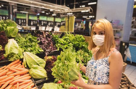 Young woman with medical protective mask and buys vegetables. Shopping during the Coronavirus Covid-19 epidemic