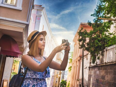 Beautiful young tourist girl in fashionable clothes takes photographs with vintage retro camera and explores city during summer holiday vacation travel .Traveler Concept image Stok Fotoğraf