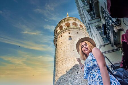 Beautiful young tourist girl in fashionable clothes poses with view of landmark Galata tower in Beyoglu,Istanbul,Turkey.Traveler Concept image