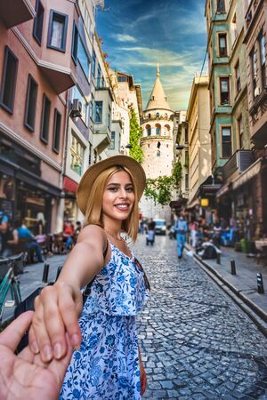Beautiful young tourist girl in fashionable clothes hold her couple hand with view of landmark Galata tower in Beyoglu,Istanbul,Turkey.Traveler Concept image Stok Fotoğraf