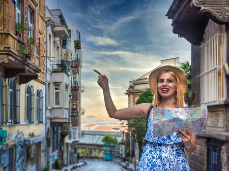 Beautiful young tourist girl in fashionable clothes with map walks around at street and explores city in summer season.Traveler Concept image