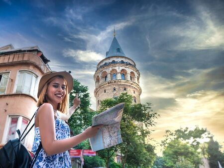 Beautiful young tourist girl in fashionable clothes with map enjoys view of landmark Galata tower in Beyoglu,Istanbul,Turkey.Traveler Concept image