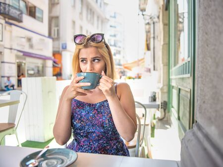 Beautiful woman drinks coffee or cappuccino while sitting a street cafe.