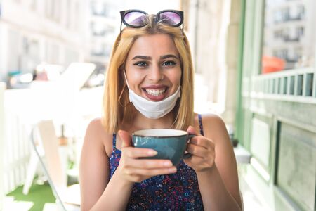 Beautiful woman wearing disposable face mask drinks coffee or cappuccino.Life with new normal during covid19 outbreak