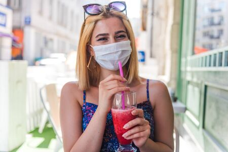 Beautiful tourist woman wearing disposable face mask drinks fruit smoothie. Life with new normal during covid19 outbreak