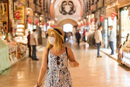 Beautiful tourist woman wearing disposable face mask walks in Egyptian bazaar in Istanbul,Turkey.Traveler woman lifestyle Concept.in and keep social distance .Traveling during covid19 outbreak