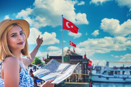 Beautiful young tourist girl in fashionable clothes shows Turkish flag and boats with map in Eminonu, Istanbul,Turkey Stok Fotoğraf