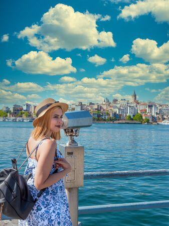 Beautiful young tourist girl in fashionable clothes looks through sightseeing binocular to Galata Tower on Galata Bridge in Eminonu, Istanbul,Turkey
