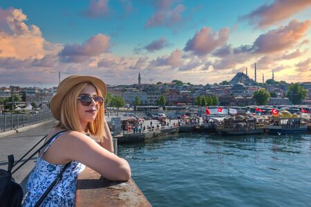 Beautiful young tourist girl in fashionable clothes poses with view of landmark Suleymaniye Mosque on Galata bridge in Eminonu,Istanbul,Turkey.Traveler Concept image Stok Fotoğraf