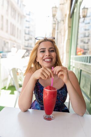 Beautiful young woman drinks  fruit smoothie while sitting a street cafe and enjoying life.