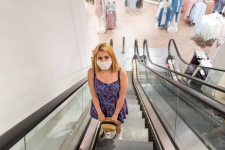 Young beautiful woman wearing face mask and keep social distance while using escalator in clothes store during covid19 outbreak.Life with new normal during covid19 outbreak.