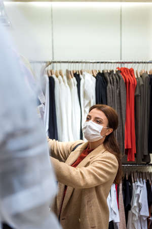 Beautiful girl wearing protective medical mask and fashionable clothes looks at clothes at store. New normal lifestyle concept.