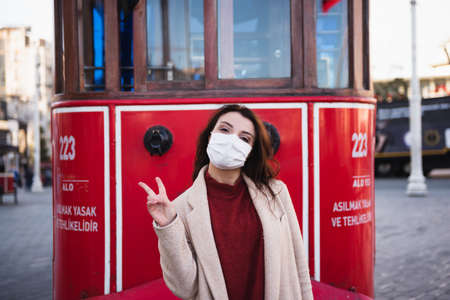 Beautiful girl wearing protective medical mask and fashionable clothes poses with red tram at istiklal street in Istanbul,Turkey. New normal lifestyle concept. Stock Photo