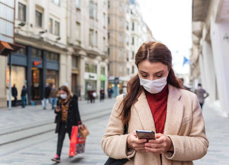 Beautiful girl wearing protective medical mask and fashionable clothes uses smart phone at street. New normal lifestyle concept.
