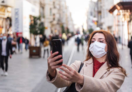 Beautiful girl wearing protective medical mask and fashionable clothes takes selfie with a smart phone at street. New normal lifestyle concept.
