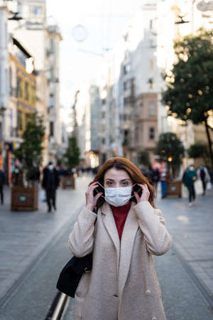 Beautiful girl in fashionable clothes holds and wears disposable mask at street. New normal lifestyle concept.