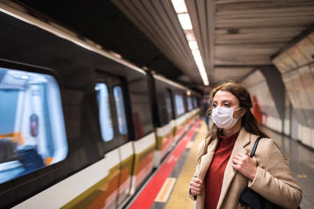 Beautiful girl wearing protective medical mask and fashionable clothes waits for train on subway platform