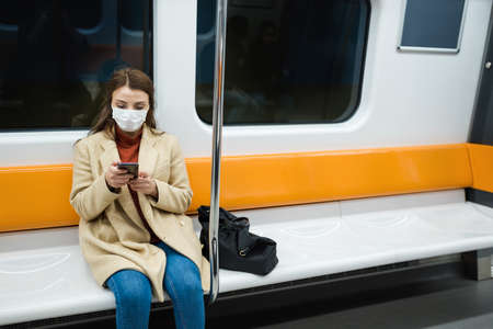 Beautiful woman wearing protective disposable mask keeps social distance and use smart phone by sitting alone while transporting.New normal lifestyle concept. Stock Photo